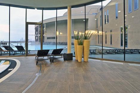 Vue de la grande baie vitrée qui sépare la piscine intérieure de celle extérieure