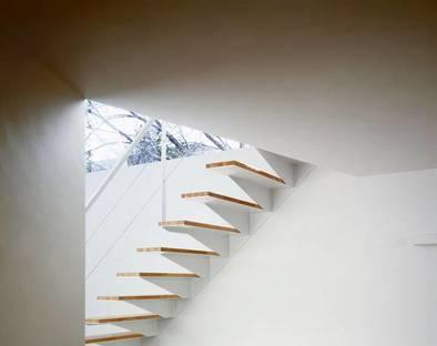 Détail de l'escalier à jour peint en blanc avec giron en bois