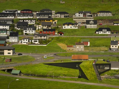 Henning Larsen signe une mairie en béton et en bois formant un pont au-dessus d'une rivière